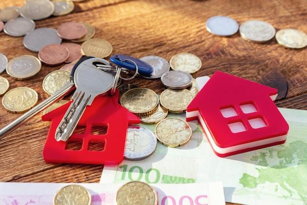 Rote hausschlüssel auf den banknoten und münzen. immobilienkaufkonzept