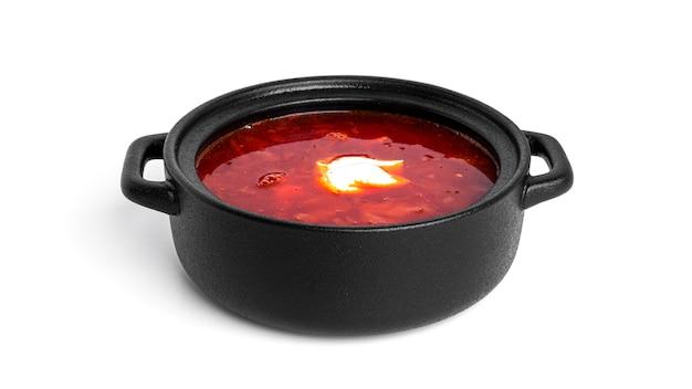 Rote, heiße borscht - rübensuppe mit saurer sahne im schwarzen topf lokalisiert auf weiß.