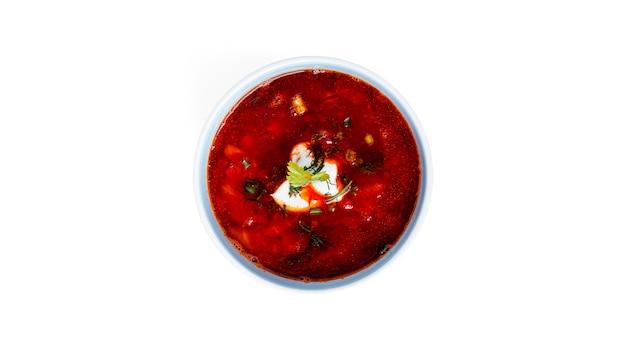 Rote, heiße borscht - rübensuppe mit saurer sahne und kräutern auf weiß isoliert.