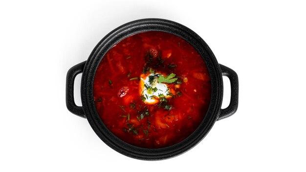 Rote, heiße borscht - rübensuppe mit saurer sahne und kräutern im schwarzen topf lokalisiert auf weiß.