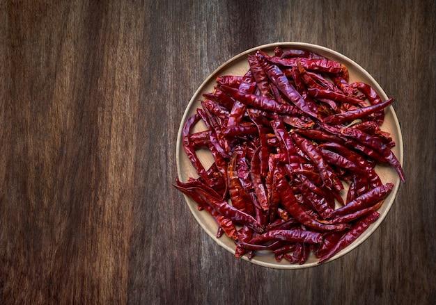 Rote heiße trockene chilischoten in holzschale auf holzbodenhintergrund, rustikaler stil
