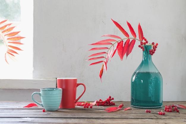 Rote herbstblätter in glasvase und viburnum-beeren und tasse tee auf holztisch