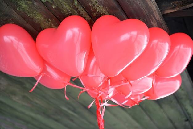 Rote herzballons für eine liebesgeschichte am valentinstag auf einem hölzernen background.coloured ballons, die ein helles hintergrundbild bilden.