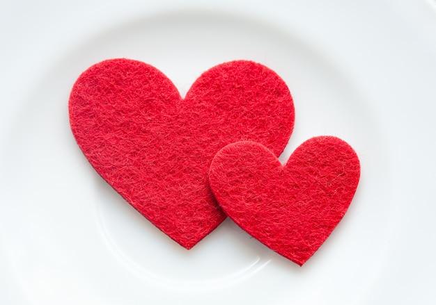 Rote herzen auf einer plattennahaufnahme. valentinstag