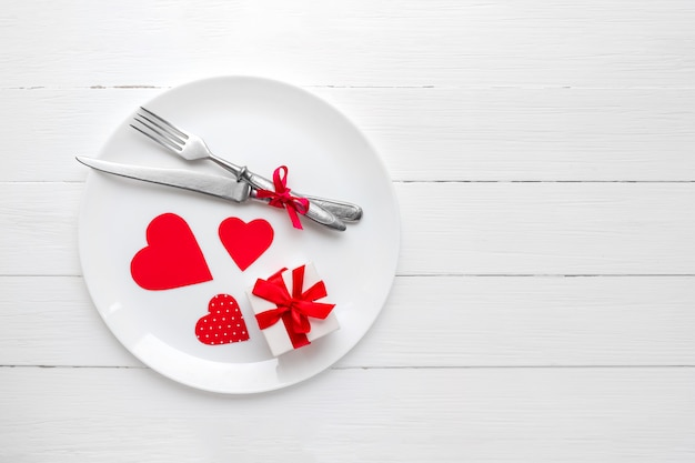 Rote herzen auf einer weißen platte mit einer gabel und einem messer und einem roten band, eine geschenkbox auf einem weißen holz