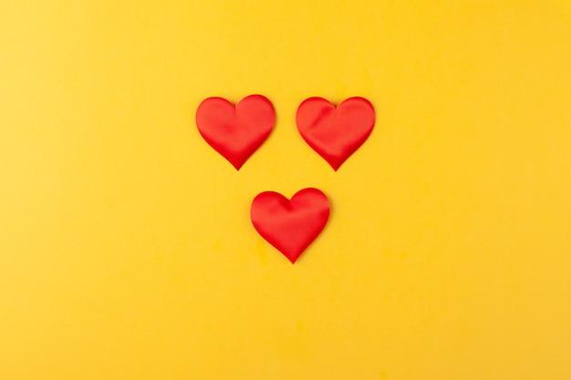 Rote herzen auf farbigem gelbem hintergrund