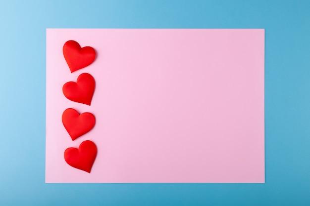 Rote herzen auf farbigem hintergrund, rosa im blauen rahmen, valentinstag-grußkartenkonzept, liebeshintergrund, romantik, horizontal, legen aus