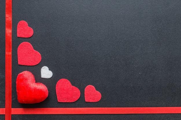 Rote herzen auf schwarzer tafel. valentinstag-konzept