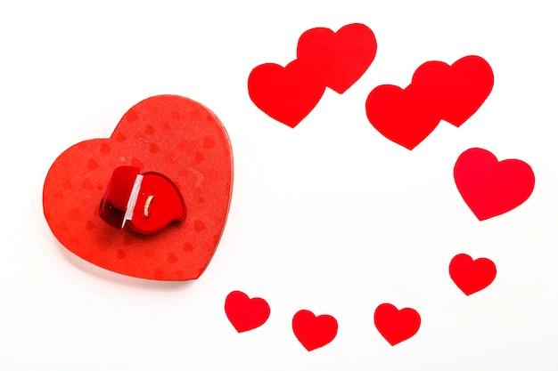 Rote herzen aus pappe verschiedener größen zum valentinstag auf weißem hintergrund und einer schachtel mit ring. horizontales foto.