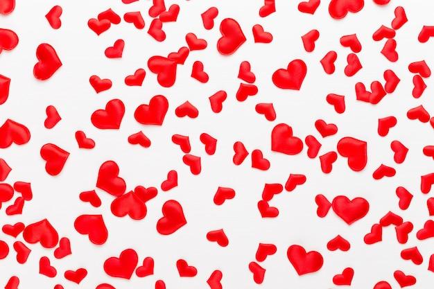 Rote herzen des valentinstaghintergrundes auf weißem hölzernem hintergrund. grußkarte.
