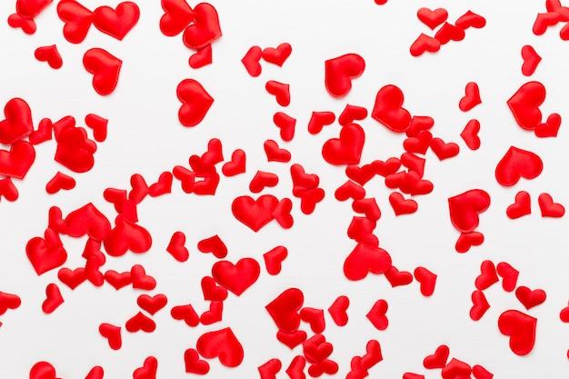 Rote herzen des valentinstaghintergrundes auf weißem hölzernem hintergrund.