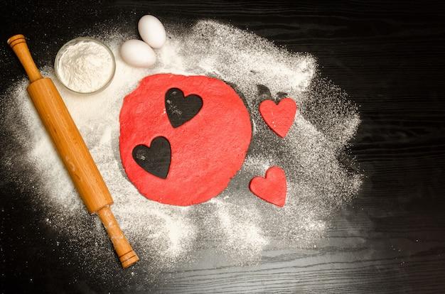 Rote herzen, die teig mit eiern, mehl und nudelholz von einer schwarzen tabelle schneiden. ansicht von oben