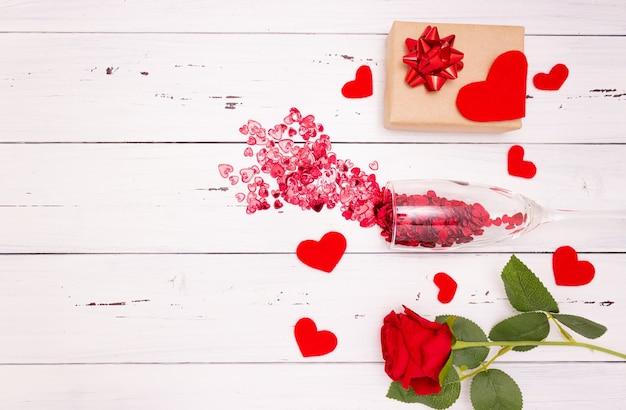 Rote herzen fließen aus champagnerglas, geschenkbox und rose