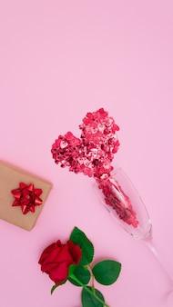 Rote herzen fließen aus einem glas champagnerglas, einer rose und einer geschenkbox