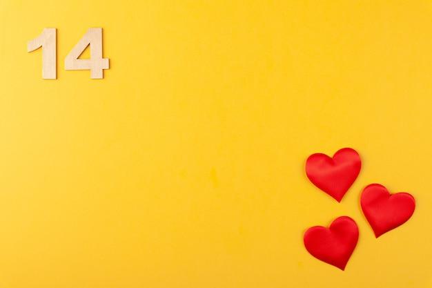 Rote herzen, goldene zahlen 14 auf gelbem hintergrund, grußkarte februar valentinstag, liebeshintergrund, romantik, horizontal, kopierraum, ansicht von oben
