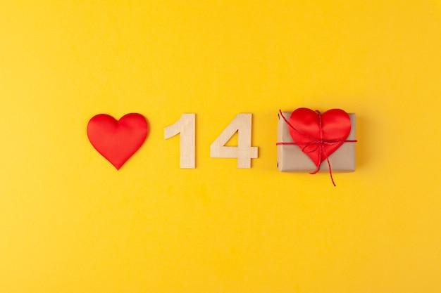 Rote herzen, goldene zahlen 14, geschenkbox auf gelbem hintergrund, grußkarte februar valentinstag, liebeshintergrund, romantik, horizontal, kopienraum, draufsicht