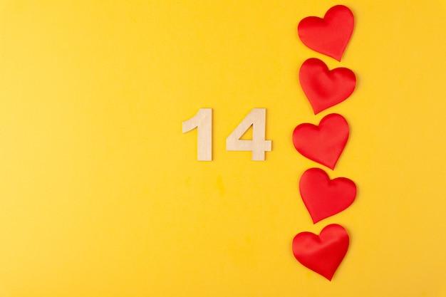 Rote herzen in der linie, goldene zahlen 14 auf gelbem hintergrund, grußkarte februar valentinstag, liebeshintergrund, romantik, horizontal, kopierraum, draufsicht