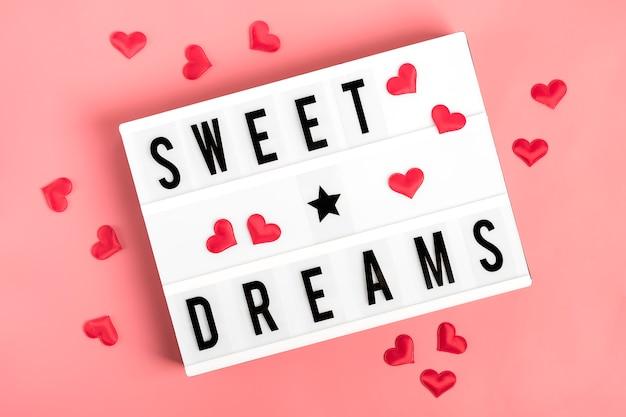 Rote herzen, lightbox mit zitat süße träume auf rosa hintergrund flache lage