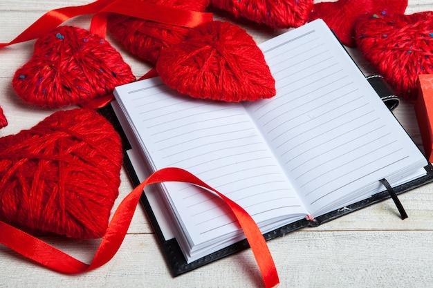 Rote herzen mit notizbuch, rotem band und papieren