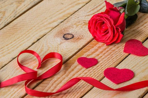 Rote herzen mit rotem band und einer rose liegen auf holztisch mit freiem textraum