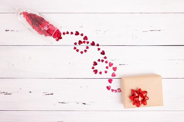 Rote herzen sprudeln aus einem champagnerglas und einer geschenkbox