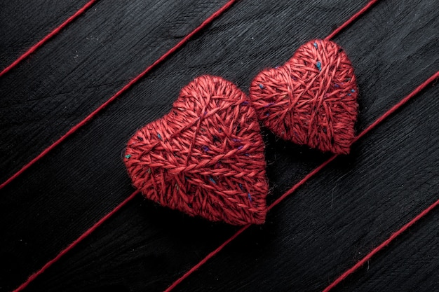 Rote herzen und fäden auf holztisch