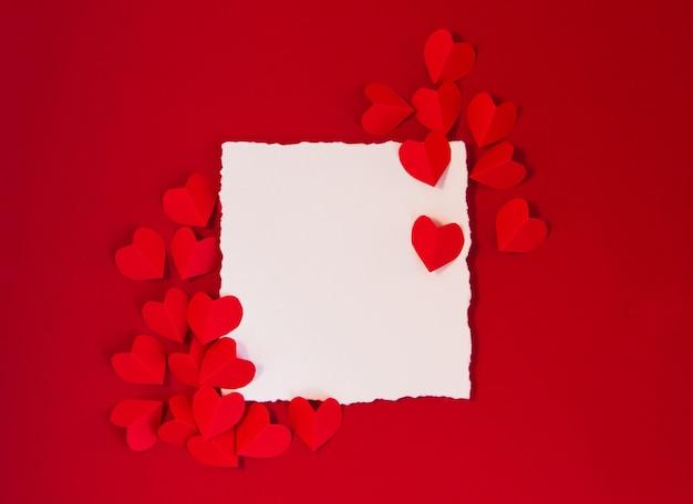 Rote herzen und karte des valentinstagkonzepts für text auf einem dunkelroten hintergrund
