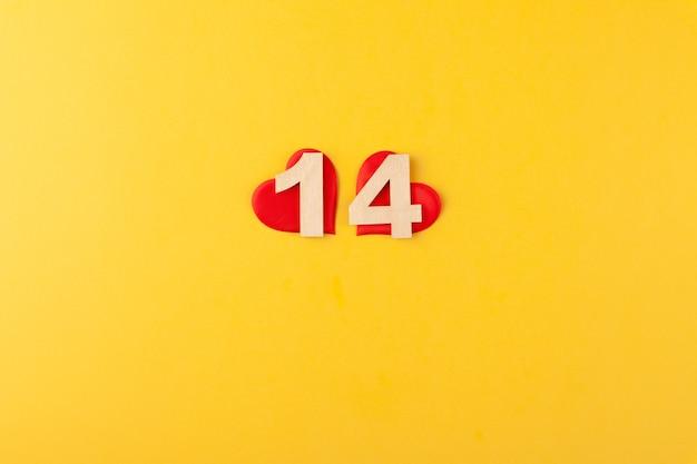 Rote herzen unter goldenen zahlen 14 auf gelbem hintergrund, grußkarte februar valentinstag, liebeshintergrund, romantik, horizontal, kopienraum, draufsicht