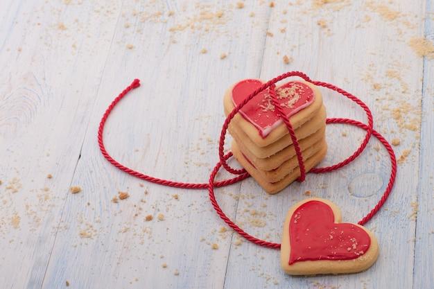 Rote herzförmige kekse im verbundenen band auf holzbrettern nahaufnahme am valentinstag