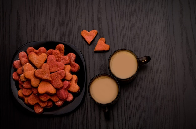 Rote herzförmige kekse und zwei tassen kaffee mit milch auf einem schwarzen tisch. valentinstag