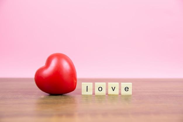Rote herzförmige luftballons mit einem hölzernen spielzeugblock mit liebestexten für valentinstag 14