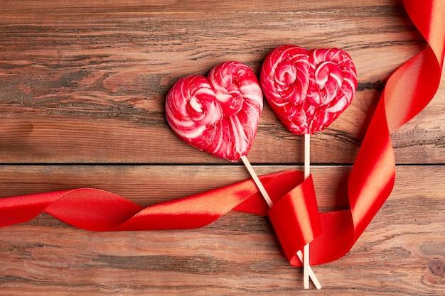 Rote herzförmige lutscher. gelocktes band in der nähe von süßigkeiten. dessert für zwei.