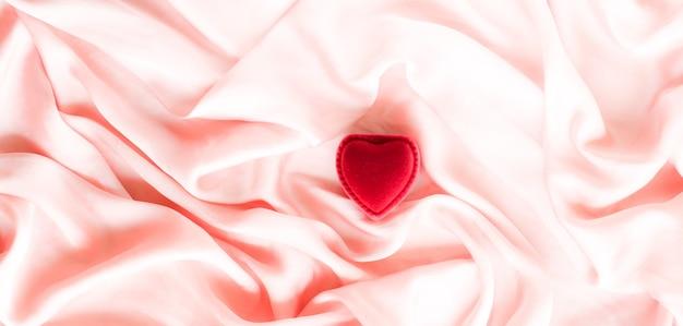 Rote herzförmige schmuck-geschenkbox auf rosa seide valentinstag wahre liebe verlobung und vorschlag ...