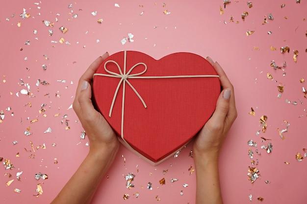 Rote herzform-geschenkbox auf festlichem rosa, in den weiblichen händen