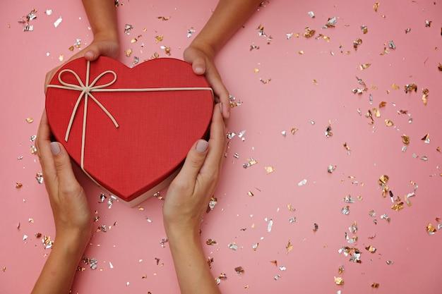 Rote herzform-geschenkbox auf festlichem rosa, mit den händen des kindes und der mutter