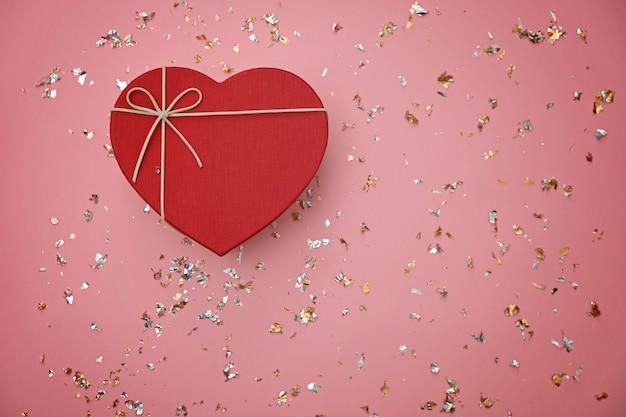 Rote herzform-geschenkbox auf festlichem rosa