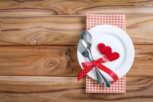 Rote herzform mit weißer leerer platte mit gabel und löffel auf holztisch für liebesabendessenkonzept