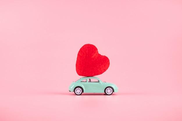 Rote herzformdekoration auf mini-autospielzeug mit kopienraum für text auf rosa. liebe, hochzeit, romantik und happy valentine day urlaubskonzept