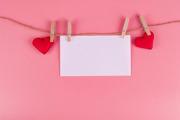 Rote herzformdekoration, die auf linie mit kopienraum für text auf rosa hängt. liebe, hochzeit, romantik und happy valentine day urlaubskonzept