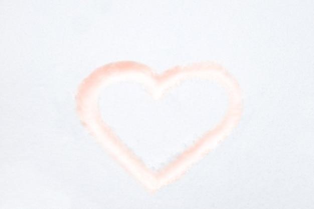 Rote herzformzeichnung auf weißem schnee als liebesvalentinsgrußhintergrund