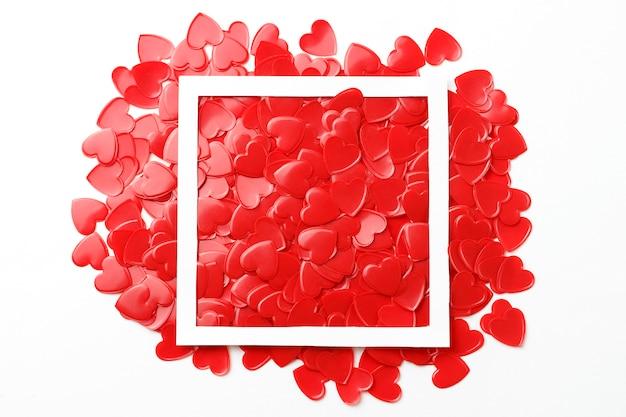 Rote herzkonfettis und weißer rahmenabschluß oben, romancekonzept, kopienraum