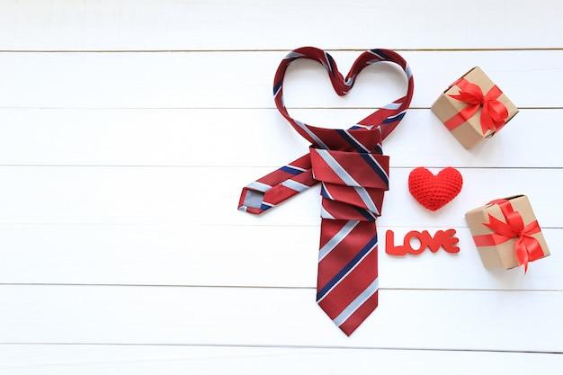 Rote herzkrawatte und -geschenkbox mit rotem band und handgemachtem häkelarbeitherzen auf hölzernem hintergrund für glücklichen vatertag