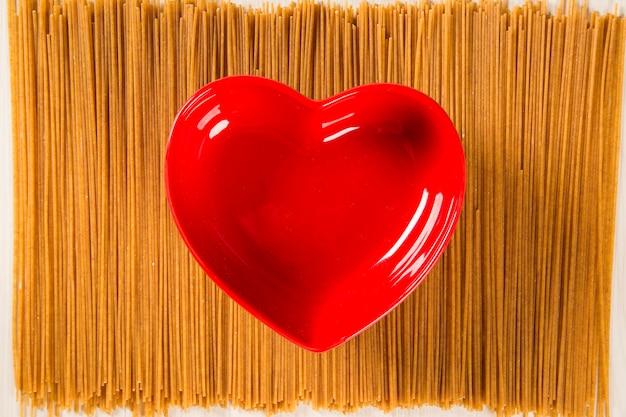 Rote herzschale auf integrierten spaghetti