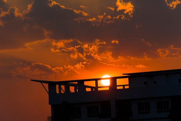 Rote himmelsilhouette eines sonnenuntergangs mit einem gebäude, das ihn blockiert.