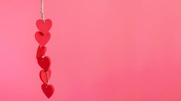 Rote hölzerne herzen, die auf dem rosa fahnenhintergrund hängen. minimalistisches kartendesign mit speicherplatz für ihren begrüßungstext zum valentinstag, muttertag oder einem anderen jahrestag.