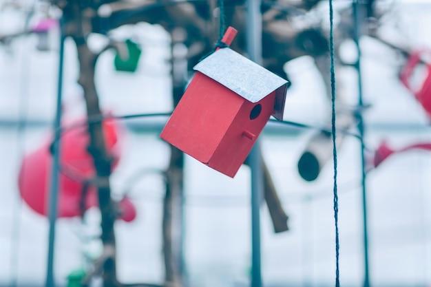 Rote hölzerne vogelhausdekoration, die am faden hängt