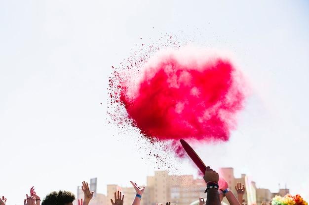 Rote holi farbexplosion über der masse