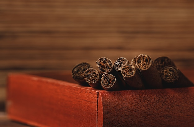Rote holzkiste mit gerollten zigarren auf holztisch schließen oben