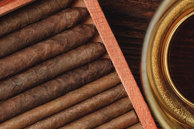 Rote holzkiste mit neuen gerollten zigarren auf holztisch schließen oben
