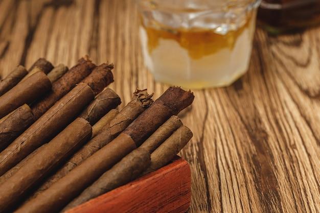 Rote holzkiste mit neuen gerollten zigarren auf holztisch